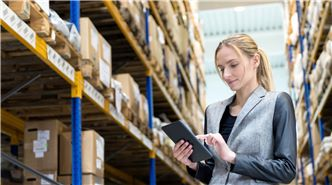 SUEZ retail facilities header image. Woman checking stock in warehouse representing facilities management sector.