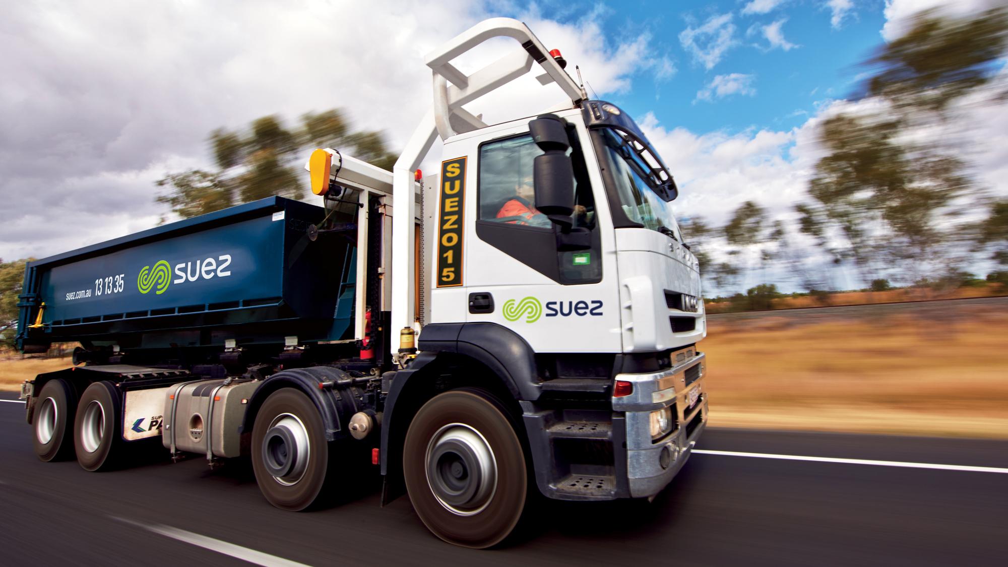 SUEZ skip bins header image. Image of SUEZ RORO truck unloading a RORO bin at an industrial area.