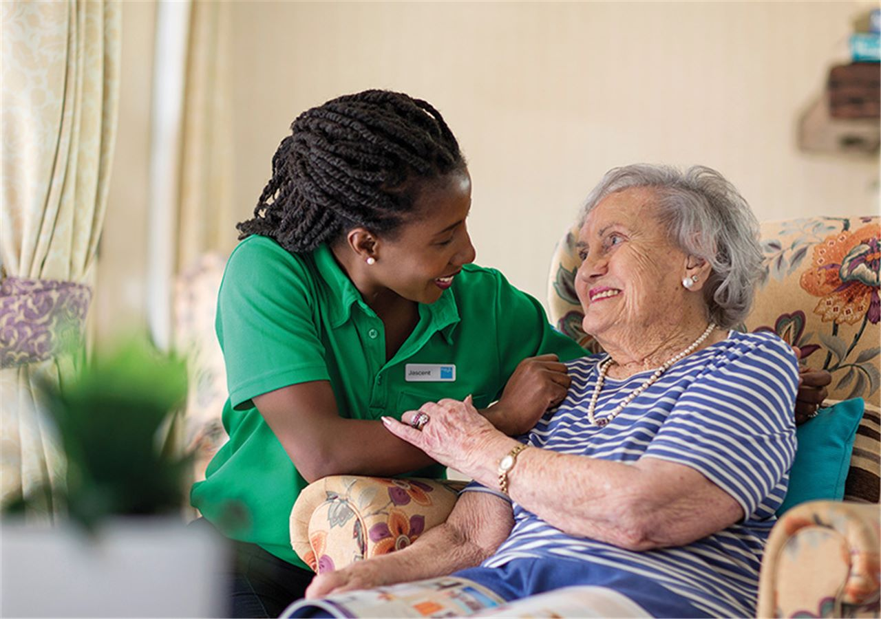 Aged Care worker and aged woman smiling at each other
