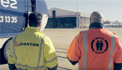 Qantas and SUEZ employees discusss business in the hangar
