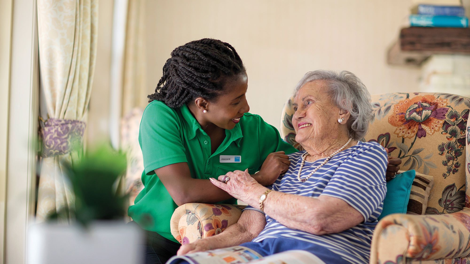 Bupa carer and resident chatting in lounge