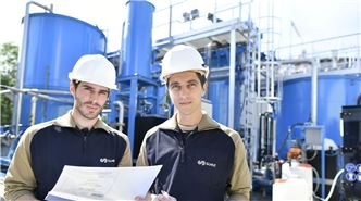 SUEZ businesses landing page image. 2 men standing in front of a SUEZ Water Treatment Facility.
