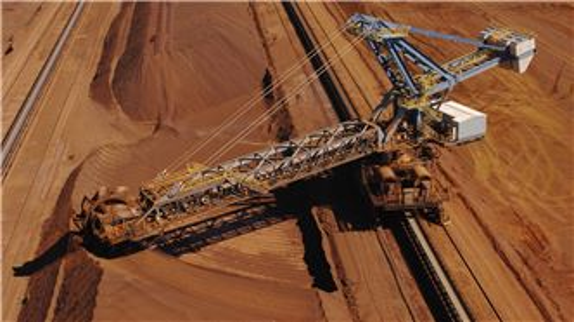 SUEZ mining & metals header. Outback Australia. Ore reclaiming machine crushing iron ore.