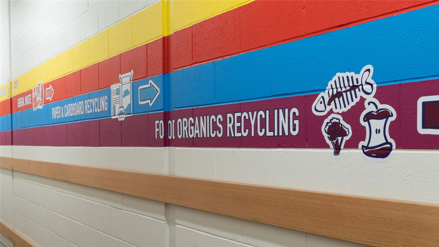 SUEZ full spectrum of waste streams management header image. Image of hallway leading to bin room showing colour coded waste stream stripes.