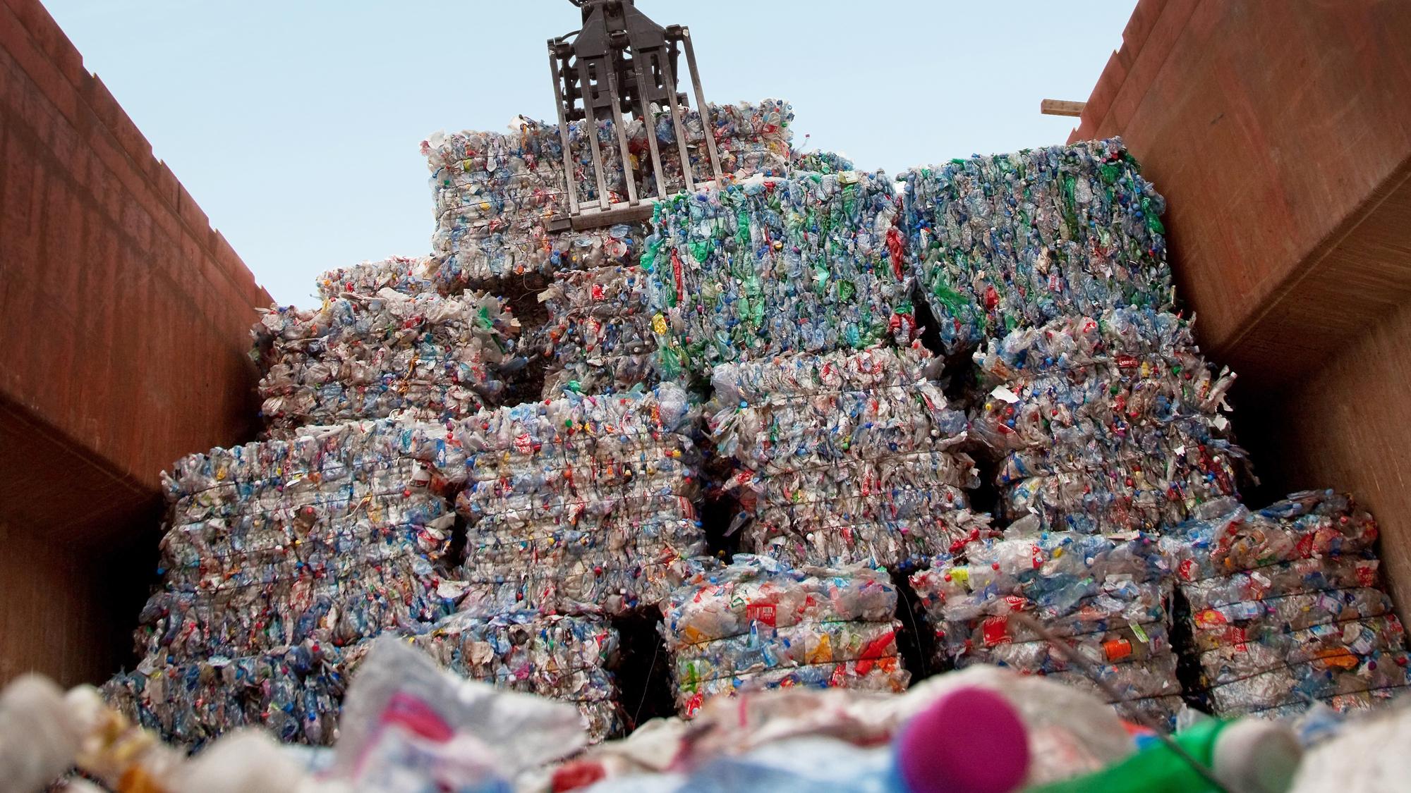 Crane loading plastic bales into container bin.
