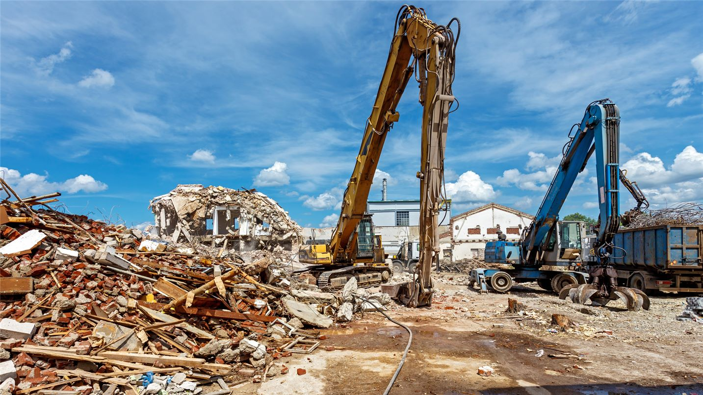 SUEZ construction and demolition services header image. Image of demolition site showing cranes and rubble.