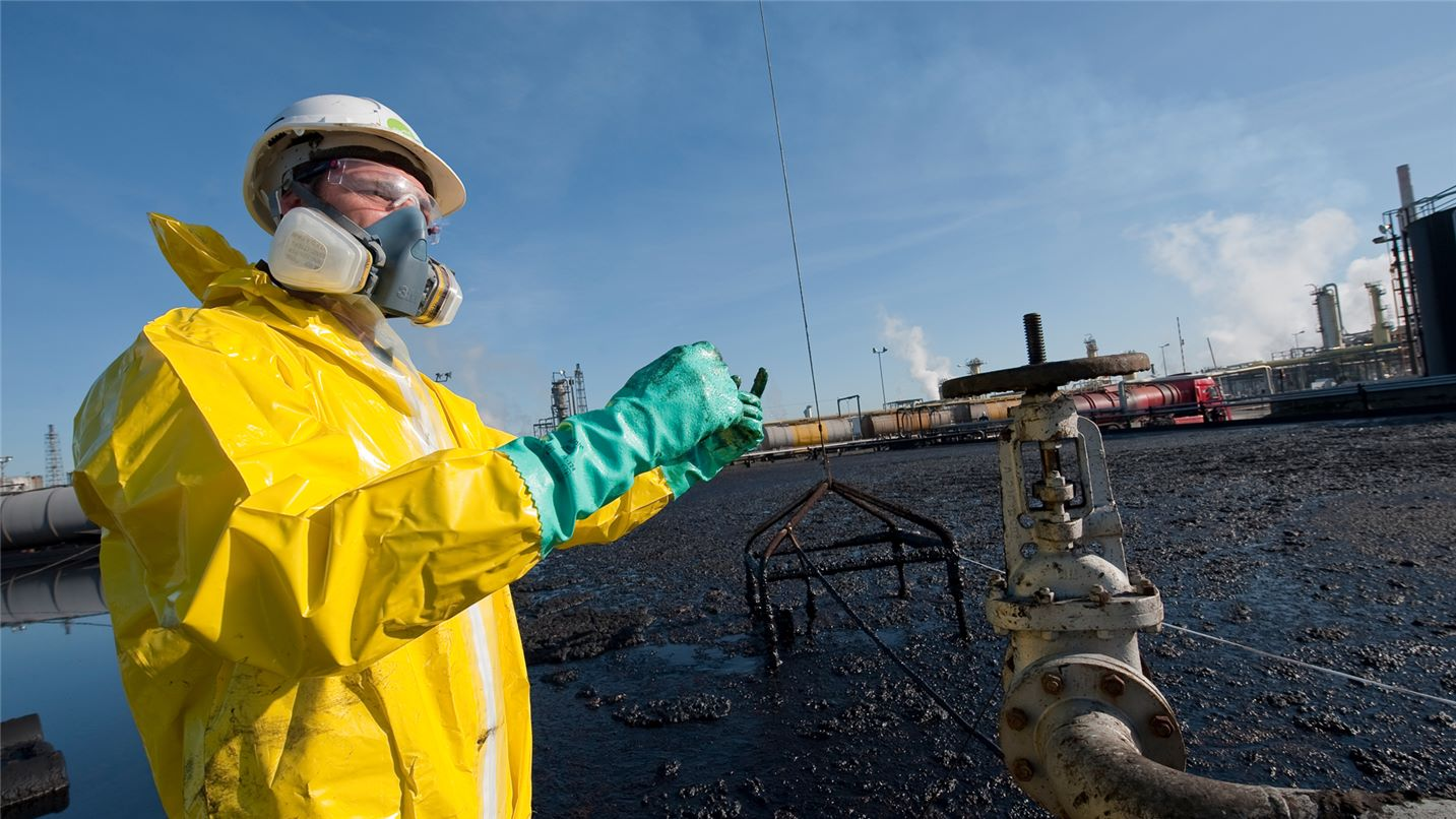 SUEZ Hazardous waste management header image. Image of worker in full yellow safety suit and respirator on site at waste facility.