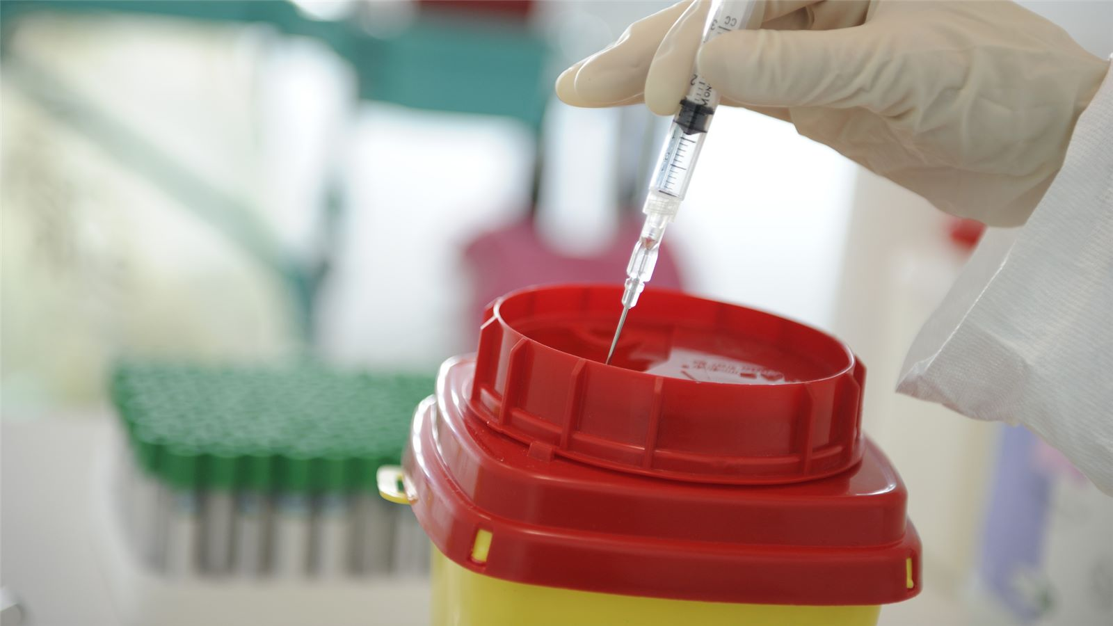 SUEZ medical and clinical services header image. Image of hand in medical safety glove placing syringe in sharps container.