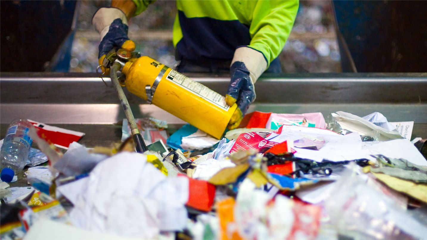 SUEZ waste assessments and audits header image. Image showing employee separating non permitted items from recycling on a conveyor.