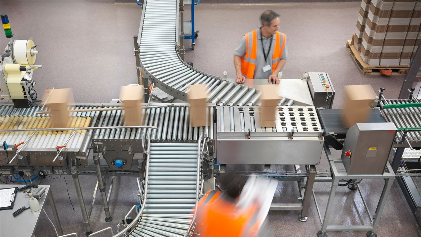 SUEZ transport and logistics header image. Men sorting boxes on conveyor in warehouse.