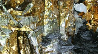 SUEZ waste management header image. Image of bale of gold plastic packaging bound for recycling.