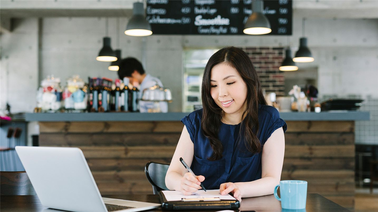 young lady taking notes in front of her laptop