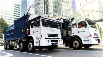 SUEZ waste collection vehicles image header. Image showing SUEZ REL and FEL trucks on a city street.