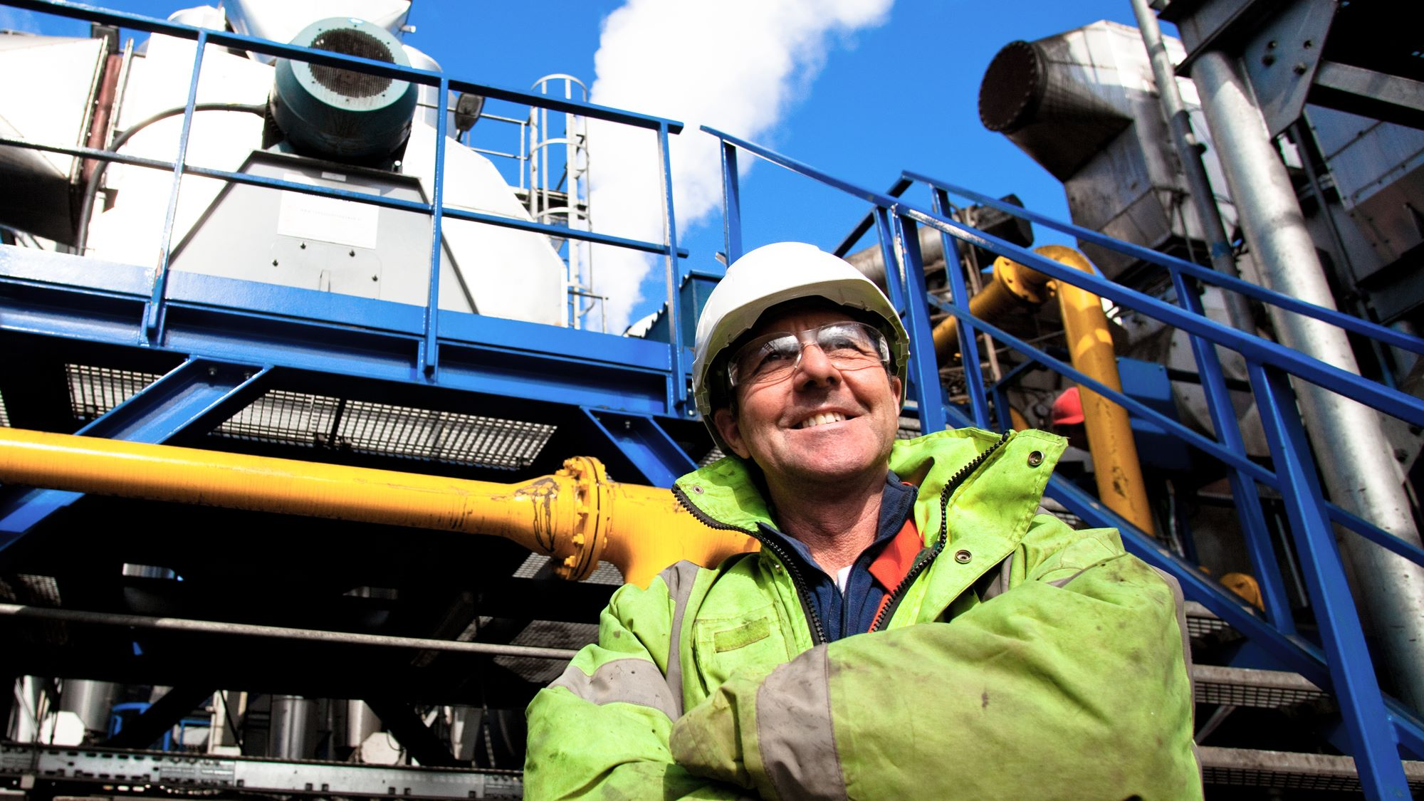 SUEZ who are you header image. Image of worker smiling  in safety hat and goggles at industrial plant