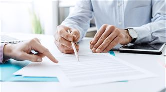 SUEZ continuous improvement header image. Image showing business people reviewing documents.