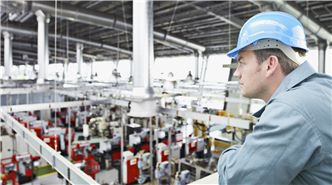 Image of worker overseeing factory work