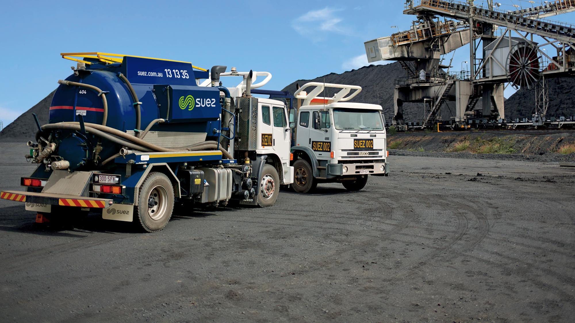 SUEZ Liquid Waste header image. Image of two SUEZ tanker trucks on a mine site.
