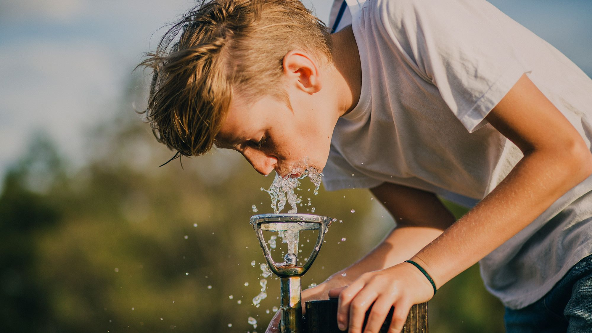 young guy drinking water from a little fountain