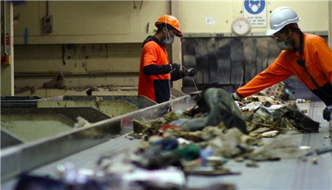 SUEZ ResourceCo header image. Two employees sorting through waste on conveyor.