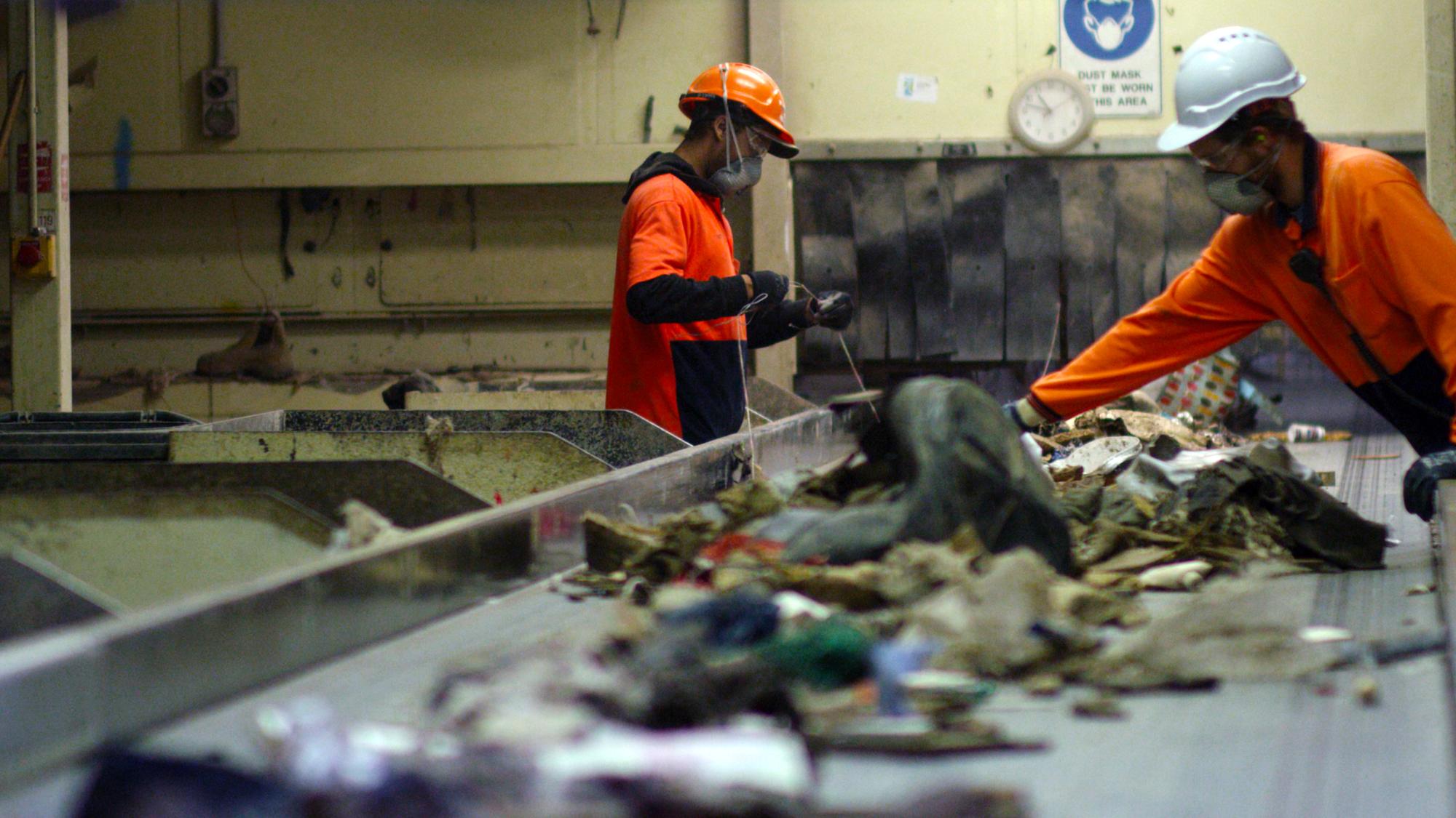 SUEZ ResourceCo header image. Two employees sorting through waste on conveyor.