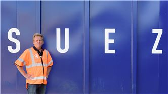 SUEZ employee in front of large blue container with SUEZ written on it
