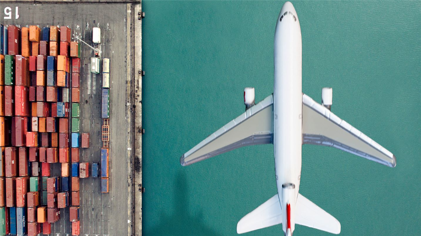 Cargo aircraft flying over shipping docks