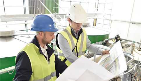 SUEZ site manager discussing plans with water treatment plant operator.