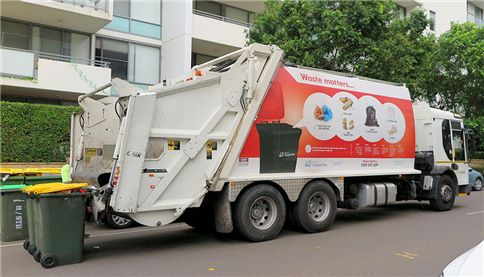 SUEZ residential collection truck lifting bins outside apartments