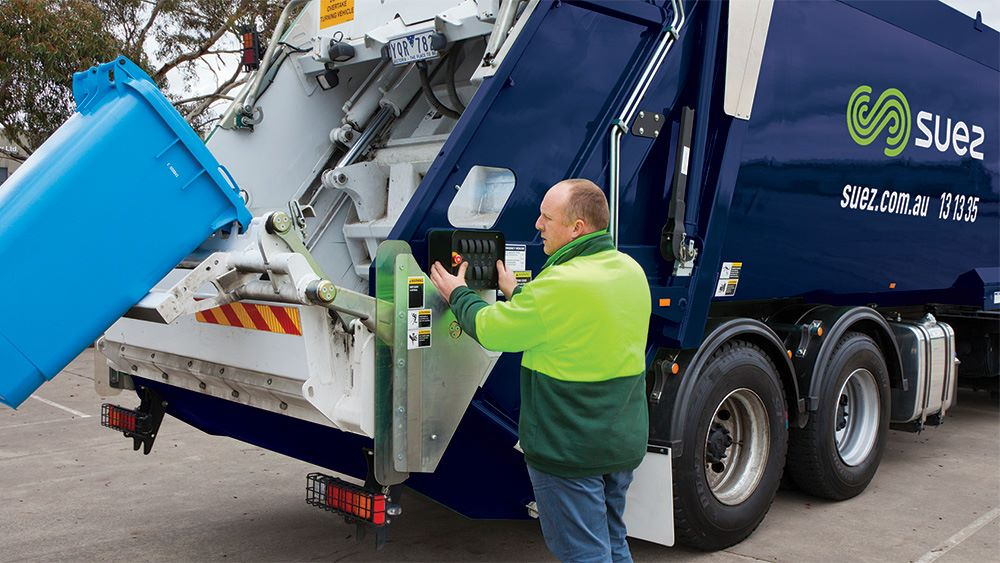 SUEZ employee emptying bin into truck