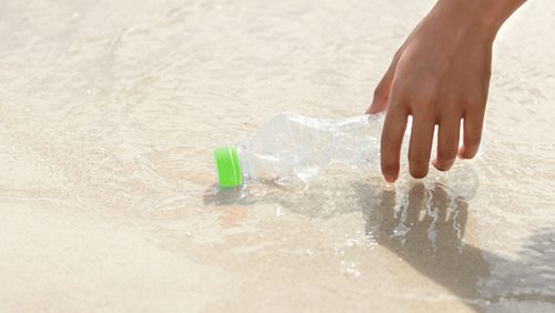 Hand pick Plastic Bottle to Recycling Garbage collection with the beach